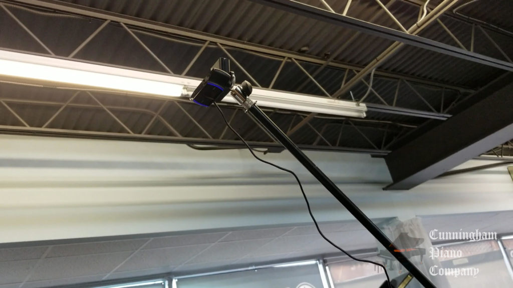 A webcam mounted on a tall mic stand